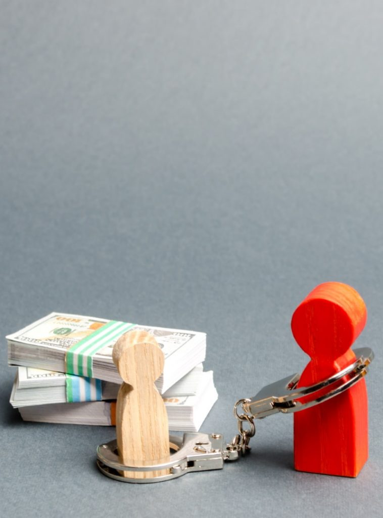 dos muñecos de madera atrapados por las deudas